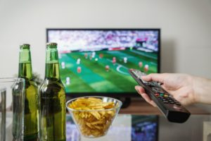 people watching television with cold drink and snacks